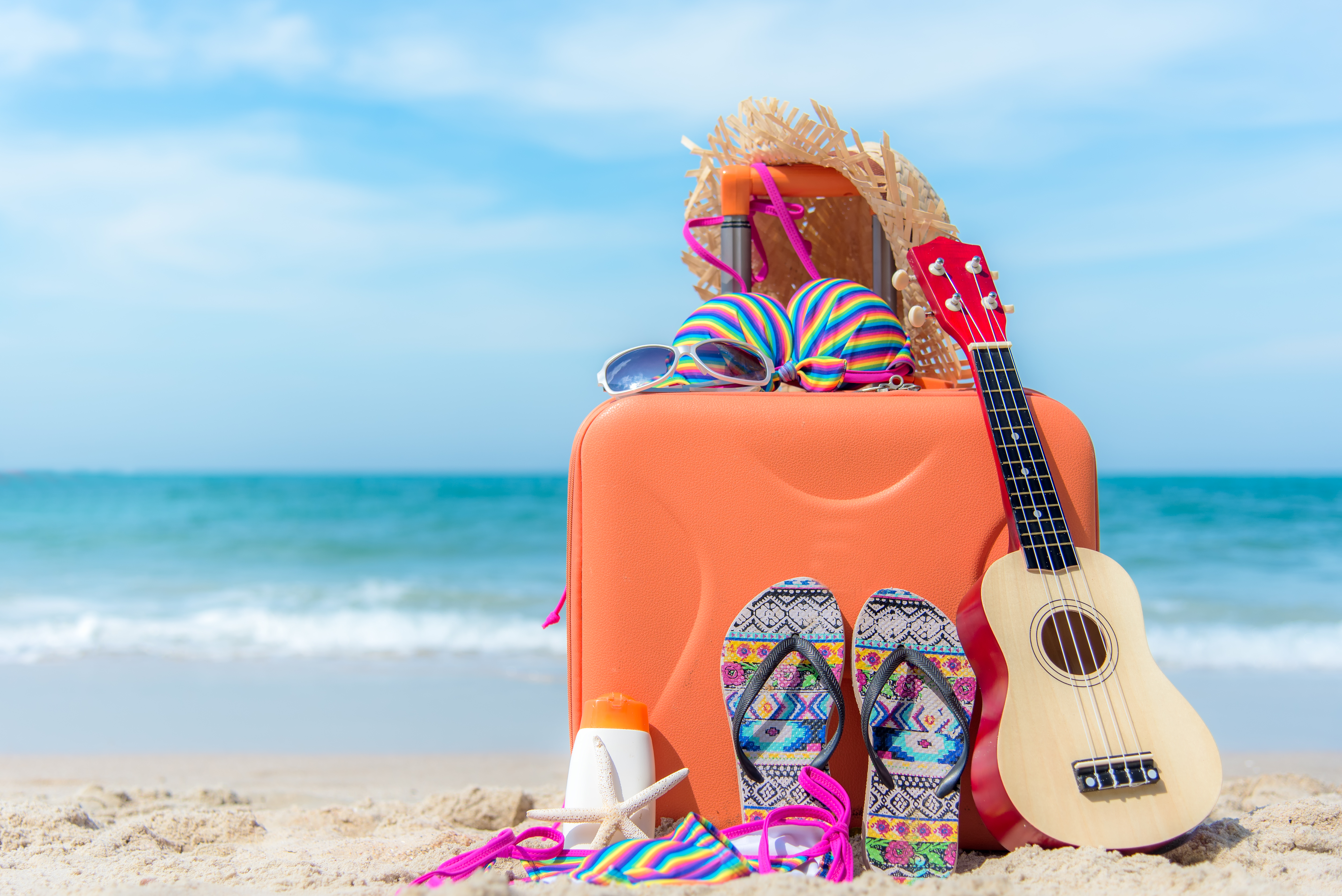Summer traveling with old suitcase and Fashion woman swimsuit Bikini,starfish, sun glasses, hat. Travel in the holiday, sunset beach background.  Summer and Travel Concept.