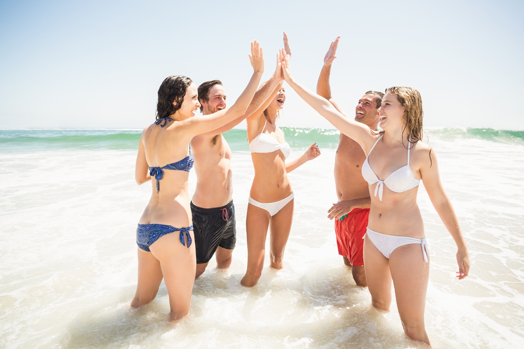 Happy friends giving a high five on the beach