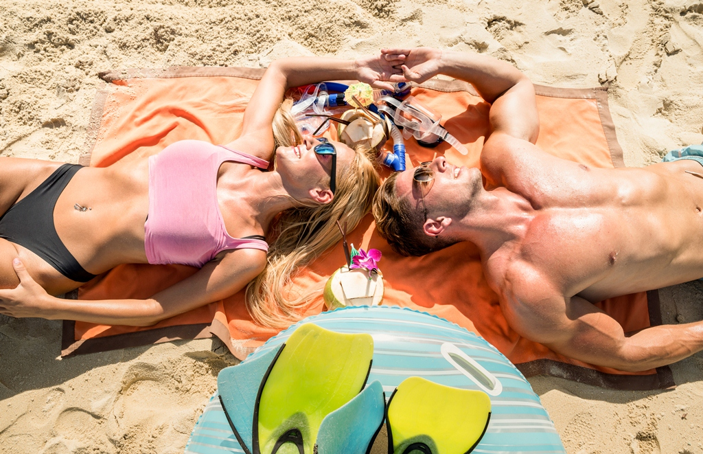 Top view of young couple vacationer having fun and relaxing on tropical Phuket beach in Thailand with coconut drink - Active youth love and travel concept around world - Bright warm color filter tones