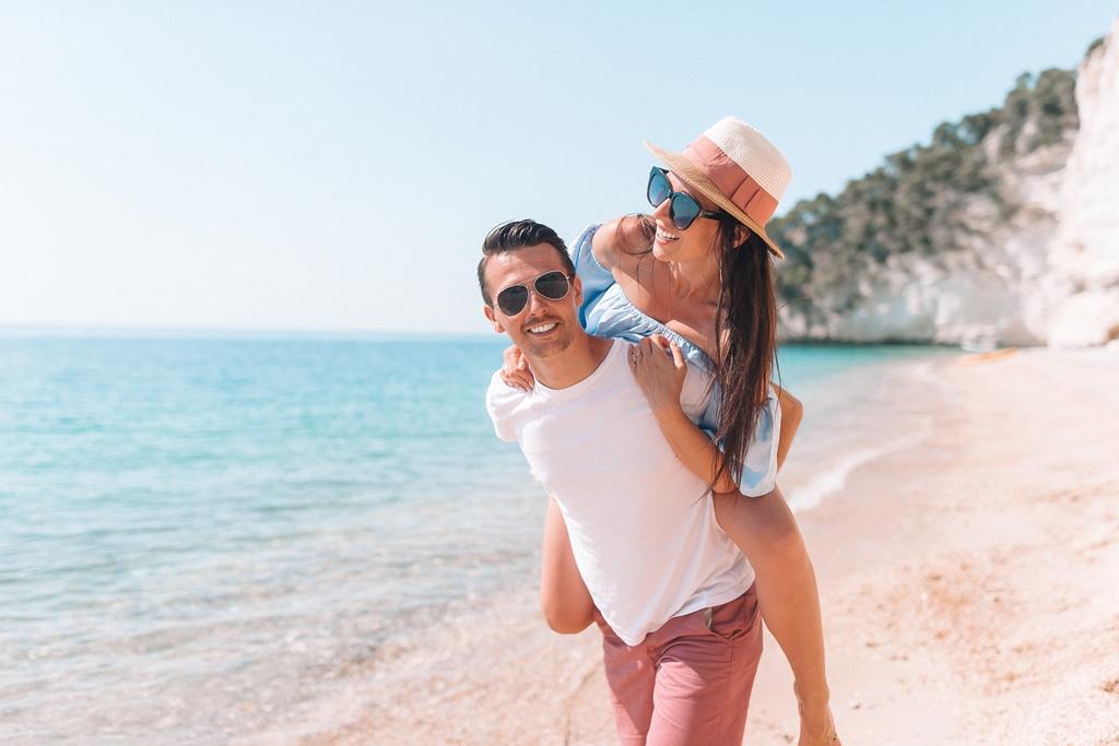 Picture of couple on white beach having fun. Happy family enjoy their honeymoon on the seashore